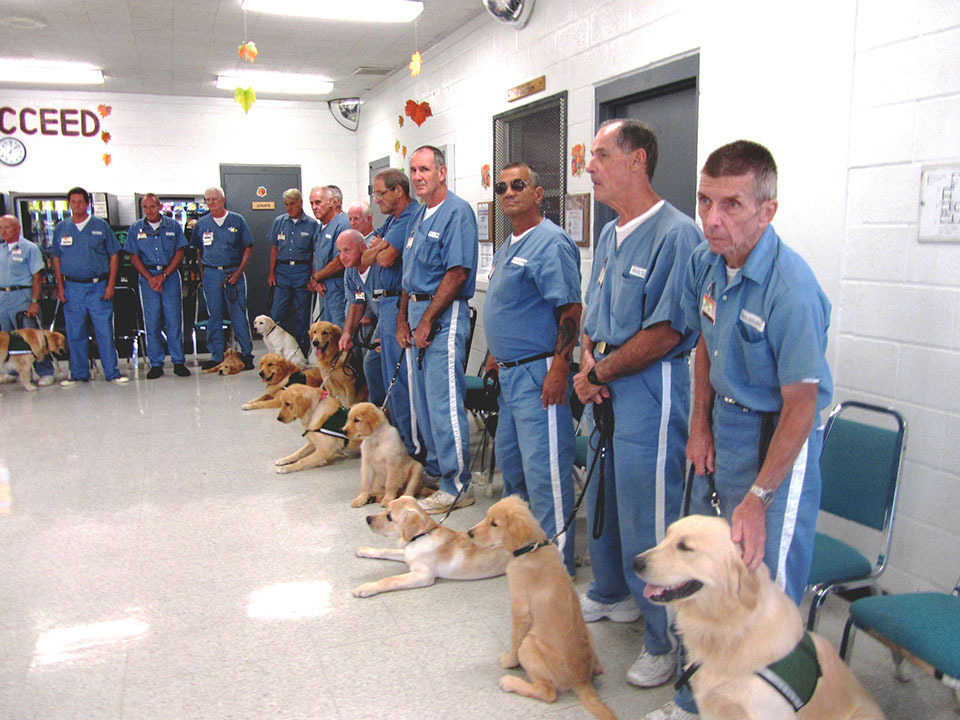 Group of incarcerated men with their prison training dogs