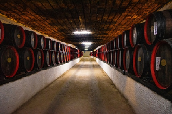 A wine cellar filled with stacked barrels of wine