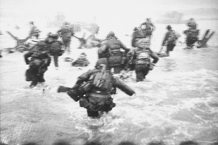 Black and white photo of troops storming the beach at Normandy by Robert Capa