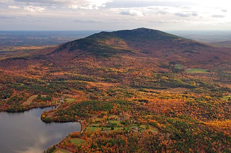 A scenic view overlooking trees with colorful leaves and Mount Monadnock