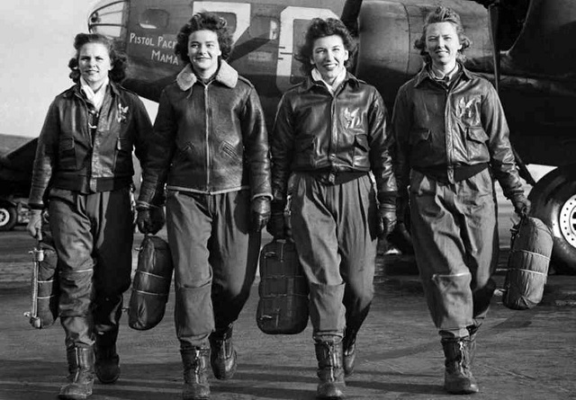 WASP pilots in flight jackets walking in front of military aircraft